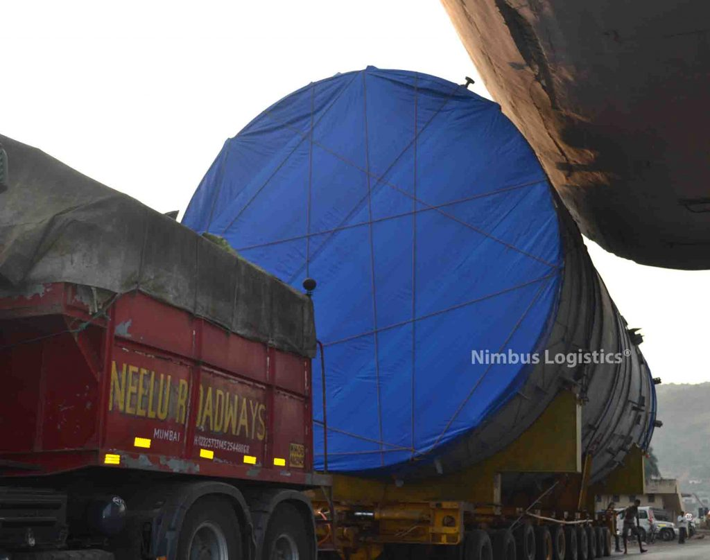 At 5.9m height, the above photo shows a Super Over Dimension Cargo being transported by Nimbus Logistics (Neelu Roadways is our sister concern). The photo shows clearing a toll gateway structure which required extending the road on the last lane by constructing a temporary extension using sand bags and bricks. The cargo was cleared with a few millimeters to spare. Volvo Puller with Hydraulic axles