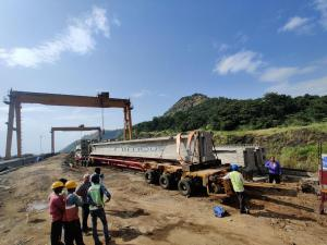 Bridge Girder being Transported on Hydraulic Axle Modular Trailer with Spacer Frame and Volvo 400 Puller